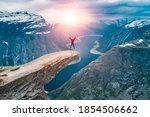 Norway, A woman Jump on the mountain's cliff edge of Trolltunga throning over Ringedalsvatnet  watching the sunset and snowy Norwegian mountains near Odda, Rogaland, Norway - stock photo