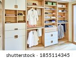 Small photo of Internal details of the wooden wardrobe with slide out rack for coathangers. Modern wardrobe with clothes hanging on slide out racks and folded on the shelves. Modern furniture