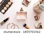 Small photo of Perfume bottle with makeup cosmetics on pink dressing table. Scent fragrance cosmetic beauty product. Beauty blogger concept. Flat lay.