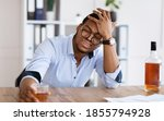 Small photo of Things getting worse, difficulties at job. Frustrated young african american businessman drinking cause of having stress, holding glass of whiskey, holding his head, office interior, copy space