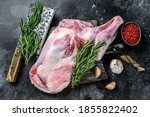 Raw lamb shoulder meat ready for baking with garlic, rosemary. Black background. Top view