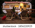 Small photo of Young couple toasting with bottles of beer near trailer. Camping season