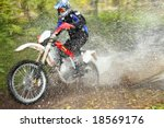 Off-road motorbike crossing river, water splashing. Motion blur. - stock photo