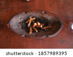 Small photo of Cigarette butts in the clay astray on the table. selective focus