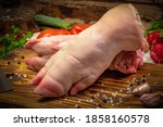 Small photo of Raw fresh pig feet, trotters on wooden board with vegetables and spices.