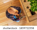 Caucasian Men in His 40s Brush Painting Backyard Garden Wooden Planter with Protectant Oil. Top View. Industrial Theme. - stock photo