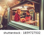 Caucasian Couple Inside Modern Camper Van During Their Wilderness Boondocking Vacation. Recreational Vehicle RV Theme. - stock photo