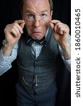 Small photo of Portrait of Old Man in Tweed Vest Putting on Spectacles. Vintage Fashion. Retro Style. Senior Moment. Cranky Old Man.