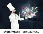 Small photo of Happy male magician chef cooking on a saucepan with flying food ingredients and smoke shaped of numbers 2021 in the kitchen