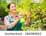 Happy Asian Woman Spraying...