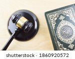 Small photo of Klang,Malaysia: 25th November 2020- Top view image of Quran with law gavel on woode background. Sharia or Islamic law concept. Large Arabic word mention the Holy Quran is with variance recitation