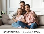 Small photo of Loving young man hug his beloved wife and little daughter sit on couch in living room, happy people smiling looking at camera posing for photo picture. Exemplary family portrait, love and bond concept