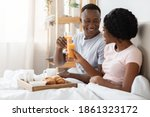 Small photo of Honeymoon concept. Happy black young couple sitting in bed in morning and having breakfast, side view, copy space. Cheerful african american man and woman enjoying breakfast in bed, talking