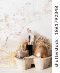Small photo of Basket with gold nail polish bottle, brush and easter golden egg. Golden nail polish bottle with gold easter egg. Easter nail polish design