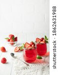 Small photo of Sweet dessert jelly pudding with strawberries in glass jar on white background