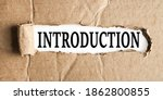Small photo of INTRODUCTION, text on white paper on torn paper background