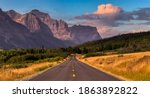 Beautiful View of Scenic Highway with American Rocky Mountain Landscape in the background. Colorful Summer Sunrise Sky. Taken in St Mary, Montana, United States.