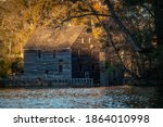 View of the old gristmill from across the millpond during golden hour at Historic Yates Mill County Park. Raleigh, North Carolina.