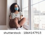 Small photo of Sad woman alone during coronavirus pandemic wearing face mask indoors at home for social distancing. Mixed race girl looking at window. Anxiety, stress, lockdown, mental health crisis concept