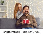 Small photo of Couple in love celebrating special date. Smiling woman covering boyfriend eyes giving him surprise gift. Happy young man getting Saint Valentines Day, Christmas or birthday present from girlfriend