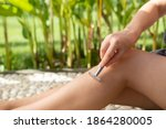 Small photo of Close up of woman shaving legs with reusable steel double edged eco-friendly safety razor outdoor over green nature background. Zero waste and sustainable plastic free lifestyle