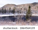 Small photo of Denuded shrubs and evergreen tree on the banks of the Jacques-Cartier National Park river, with wooded mountains in the background, Stoneham-et-Tewkesbury, Quebec, Canada