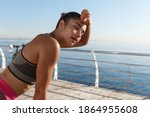 Image of beautiful young fitness woman panting and wiping sweat off forehead after jogging, finish run or workout, standing on a pier