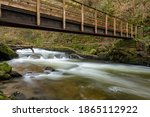 Small photo of Long exposure of the East Lyn river flowing under Lyn Rock bridge at Watersmeet in Exmoor National Park in autumn