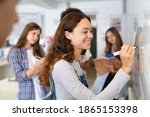 Small photo of Happy college student writing equation on white board in class. Satisfied young girl solving math problem on whiteboard with classmates in background watching her. Proud high school student writing.