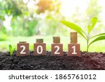 Small photo of Year 2021 economy growth and recovery, increase money saving and investment concept. Wooden blocks 2021 with increasing stack of coins at sunrise on natural background.