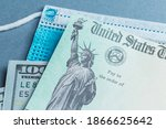 Small photo of A US stimulus check on with some one-hundred-dollar bills and a medical mask