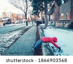 Small photo of Funny child girl in warm clothes jacket lying in snow on city street. Kid having fun making snowball on cold winter day. Naughty cranky kid playing outside. Hilarious funny weird kid outdoor.