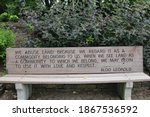 A wood bench engraved with an inspirational quote from Aldo Leopold in a park in Janesville, Wisconsin, USA