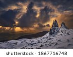 Old Man Storr, Isle Skye, Scotland. Winter, very snowy mountain in a very powerful sunrise with some storm clouds in the middle of the sunrise. Very interesting hot and cold contrasts.Commercial shoot