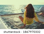 Woman Sits On The Deck Of A...