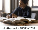 Small photo of Remote learning. Diligent millennial mixed race female student prepare for exam at home. Confident indian woman write up notes thesis for research report essay. Focus on opened paper books on table