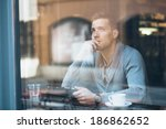 pensive young man using tablet... | Shutterstock . vector #186862652