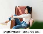 asian woman listening to music... | Shutterstock . vector #1868701108