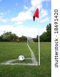 Soccer Ball on the Corner of Field under Blue Sky - stock photo