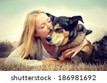 Stock photo young woman and her german shepherd dog lying in the grass she is hugging and kissing him vintage 186981692