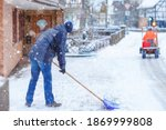 Man with snow shovel cleans...
