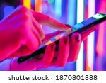 Small photo of Woman using smartphone device at interactive exhibition or museum with purple illumination - scrolling and touching - close up view. Futuristic, retrowave, immersive, entertainment concept