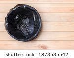 Small photo of Empty Bin on Wooden Background. Trash Can Top View. Garbage Basket. Rubbish Black Bag in a Trash Can. Empty Rubbish Bin. Waste Can with Plastic Package. Empty Garbage Bin. Bin on Wooden Floor. Trash