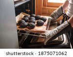 Small photo of Failed cooking in oven. Woman holding a tray of spoiled muffins