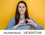 Small photo of Cheerful cute young woman having wide charming smile put hands on chest make with fingers heart shape symbol of charity, isolated on yellow studio background. Generosity liberality sign concept