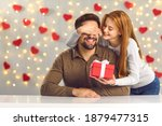 Small photo of Young couple in love celebrating Saint Valentine's Day or relationship anniversary. Happy woman covering boyfriend's eyes giving him surprise gift. Smiling man getting present from loving girlfriend