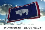 Wyoming flag on a flagpole waving in the wind, blue sky background. 3d rendering.