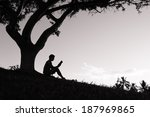 Silhouette Of Boy Reading Book...