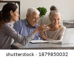 Small photo of Female banking specialist consult happy mature couple about loan or mortgage at meeting in office. Woman consultant advise recommend elderly spouses good medical life health insurance on computer.