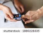 Small photo of Close-up photo of a female hands. Woman doctor measures the patient's pulse and oxygen saturation to middle aged woman using a pulse oximeter, healthcare concept